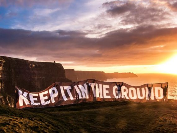 Activists hold a 'keep it in the ground' banner on the Cliffs of Moher in Ireland.